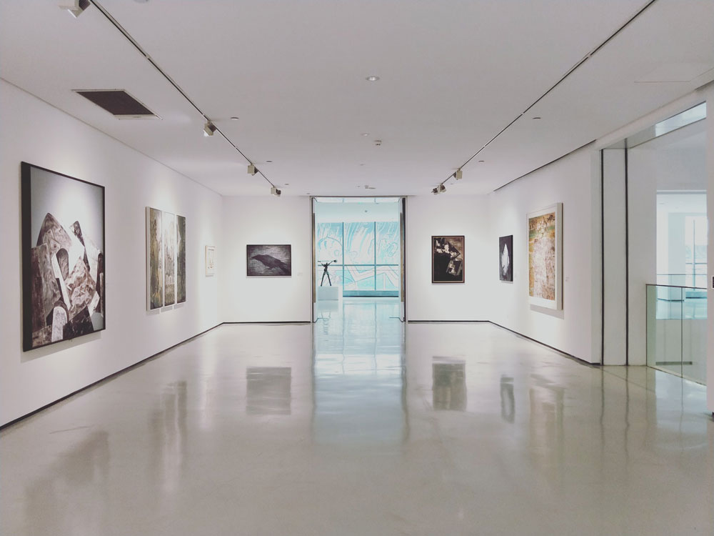 Empty art gallery with bright white walls with artwork adorning the walls.